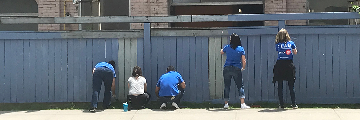 Employees painting a fence at BMO Volunteer Day 2019