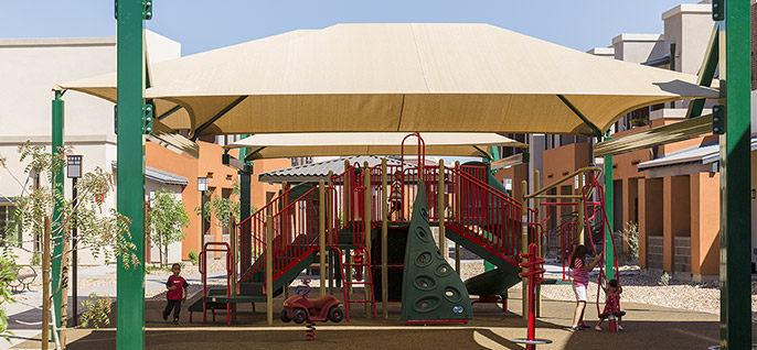 Children playing in the Madison Heights community playground in Avondale, Arizona. BMO provided construction loans for this public housing community.