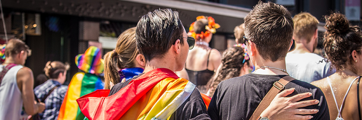 Two people walking at a Pride parade and one is wearing a cape with Pride colors