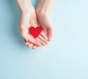 A pair of hands holding a red felt heart