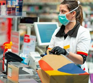 A cashier at the checkout wears a mask and gloves