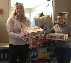 Two women holding boxes of donuts in front of pantry items for donation