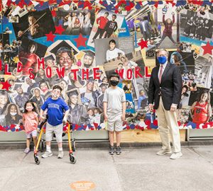 Dave Casper stands in front of the mural with three school children
