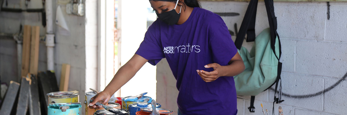 A woman with a mask selecting paint for the mural