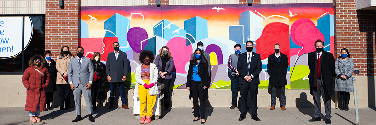 A group of people wearing masks in front of the mural outside BMO's Lake Street branch in Minneapolis
