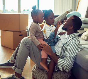Two little girls sitting on their father's lap facing him