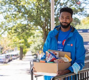 A BMO employee with a box of groceries