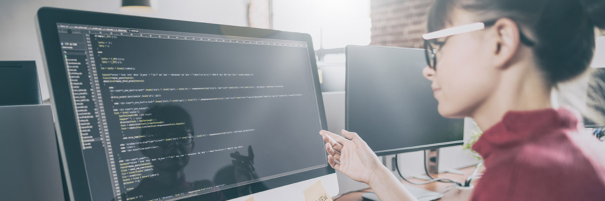 A woman reviews programming code on her computer