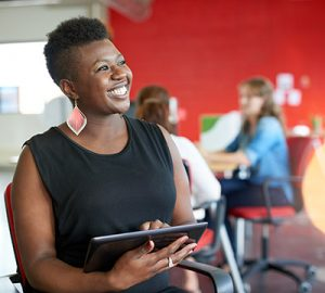 A woman of color holding a tablet and smiling