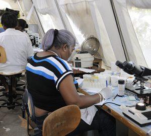 An Haitian pathologist testing patients' blood samples