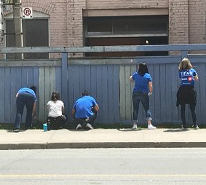 BMO employees painting a fence at BMO Volunteer Day 2019