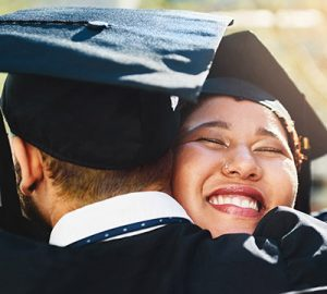 Two people in their graduation gowns hugging
