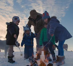 An adult watches over four children as they roast marshmallows by the campfire