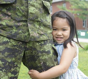 A little girl is standing beside someone in camouflage uniform