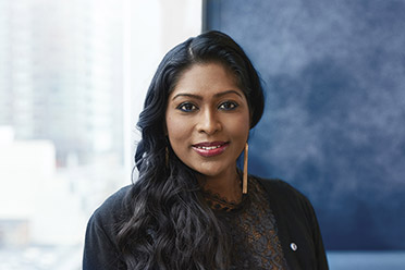 A BMO Employee, Asia Shahulhameed, stands by a window smiling
