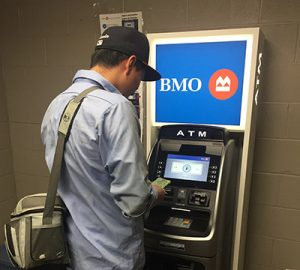 A farm employee using a BMO ATM