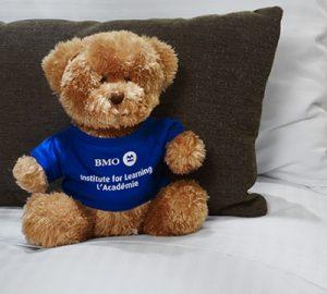 A stuffed bear toy in a BMO sweater