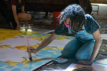 A student paints the mural