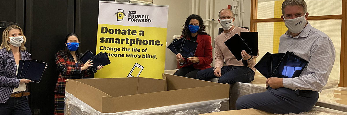 Members from the CNIB and BMO teams stand together beside a large Phone It Forward Banner. In the foreground are boxes full of donated iPads. From left to right, Suzanne Decary, Executive Director, Ontario South for CNIB, Tanya Thung and Rosemary Torelli from BMO Financial Group, Gary Nenson, Vice President, Philanthropy for CNIB and John M. Rafferty, President and CEO for CNIB. Each person holds a few iPads in their arms.