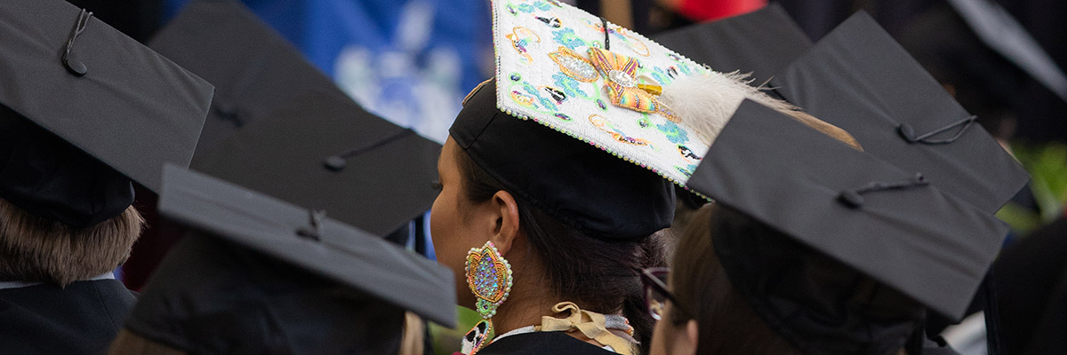 A colourful graduation cap stands out in a sea of black graduation caps
