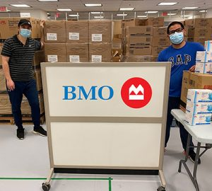 Two people standing in front of boxes of surgical masks