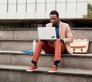 A man sitting on the steps working on his laptop