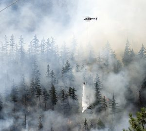 A helicopter releases water to help put out a wildfire